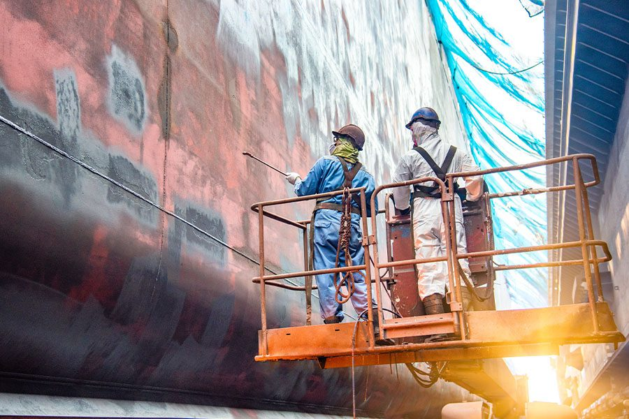 Marine Contractor Insurance - Steel Basket Carrying Workers by Crane to Clean and Repair a Ship