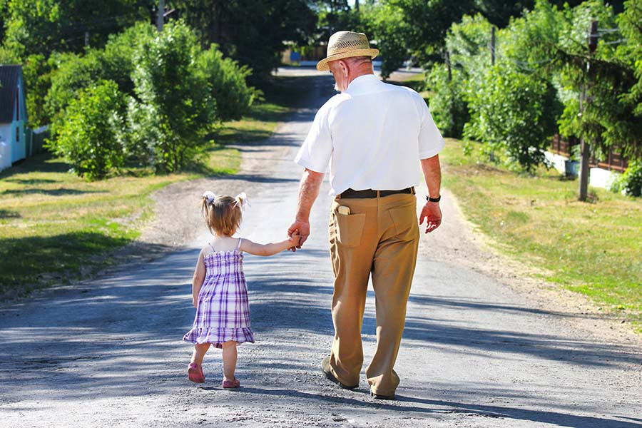 About Our Agency - View of a Grandfather Walking with His Granddaughter on an Empty Country Road While Holding Her Hand