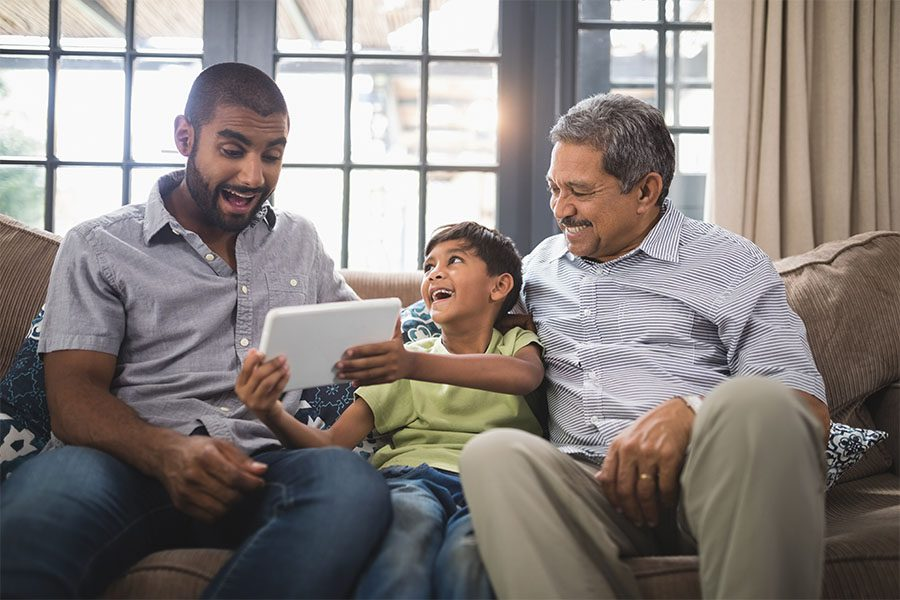 Client Center - Portrait of Cheerful Father and Grandfather Sitting on the Sofa While a Young Boy Shows Them His Tablet