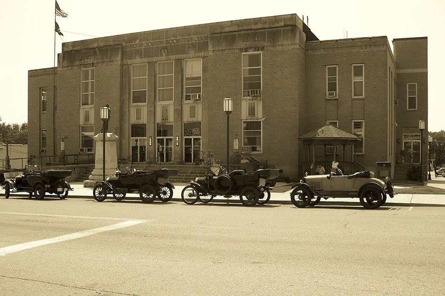 Our History - Vintage Photo of Downtown McArthur Ohio with Row of Antique Cars Parked Next to a Commercial Building