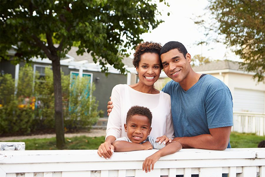 Personal Insurance - Portrait of Happy Family with a Young Son Standing Next to a White Picket Fence in Front of Their New Home