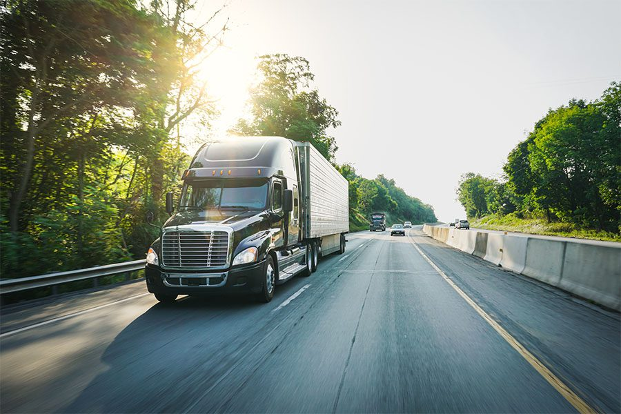 Specialized Business Insurance - View of a Black Tractor Trailer Truck Driving on a Highway with the Sun Shining Through the Green Trees