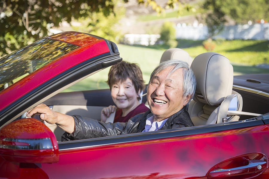 Client Center - Senior Couple in a Red Convertible, Smiling, Surrounded by Greenery