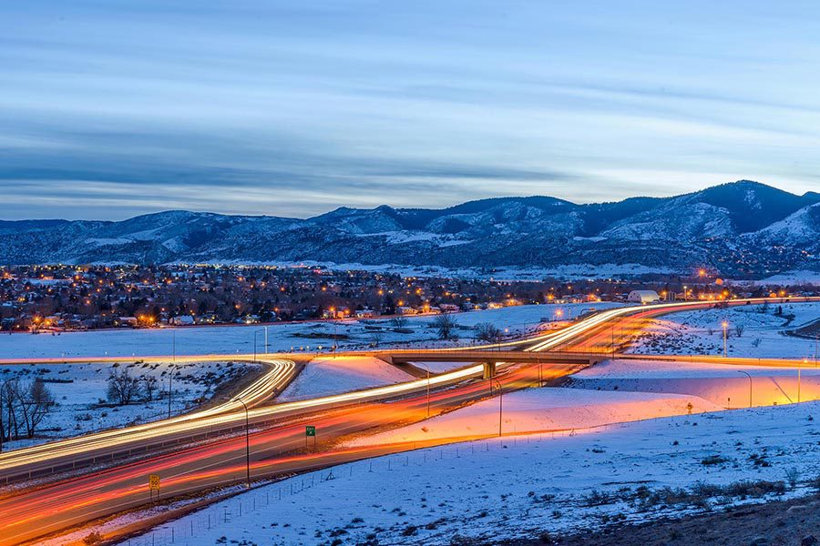 Littleton, CO Insurance - Long Exposure of Denver, Colorado at Night, Traffic Rushing By, Homes Lit up for the Evening, Snow Covered Mountains Above