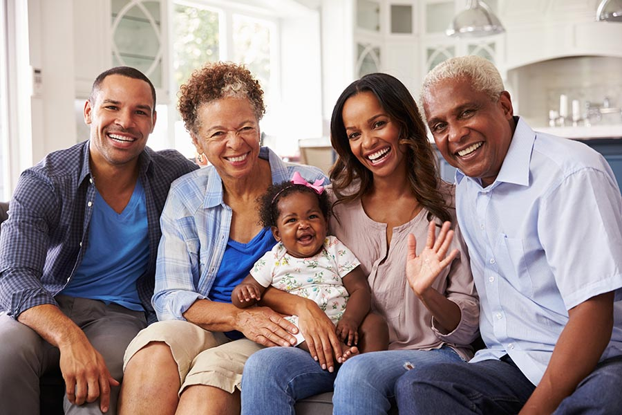 Personal Insurance - Parents, Baby Girl, and Grandparents on a Couch Together in a Beautiful Living Room