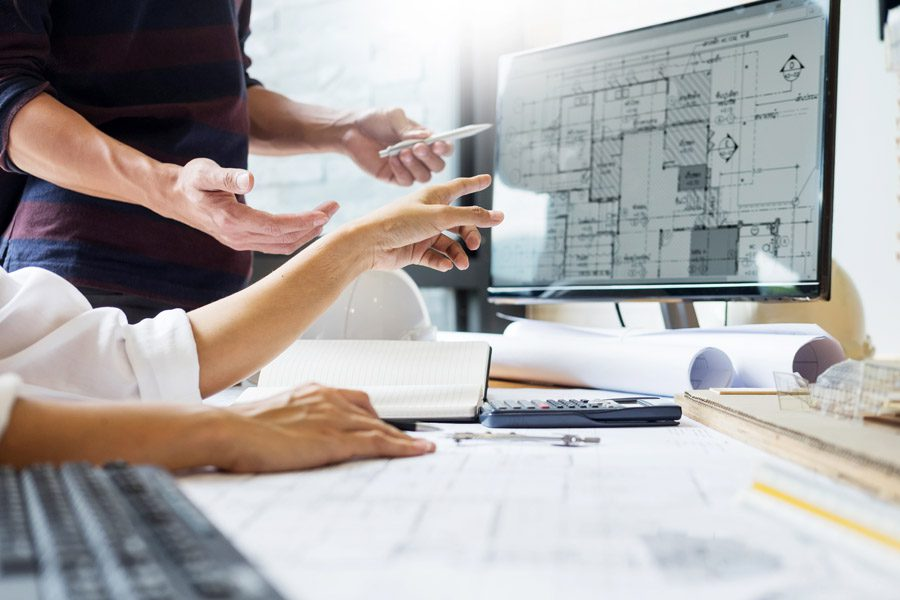 Builders Risk Insurance - Builder with Plans Looking at a Computer
