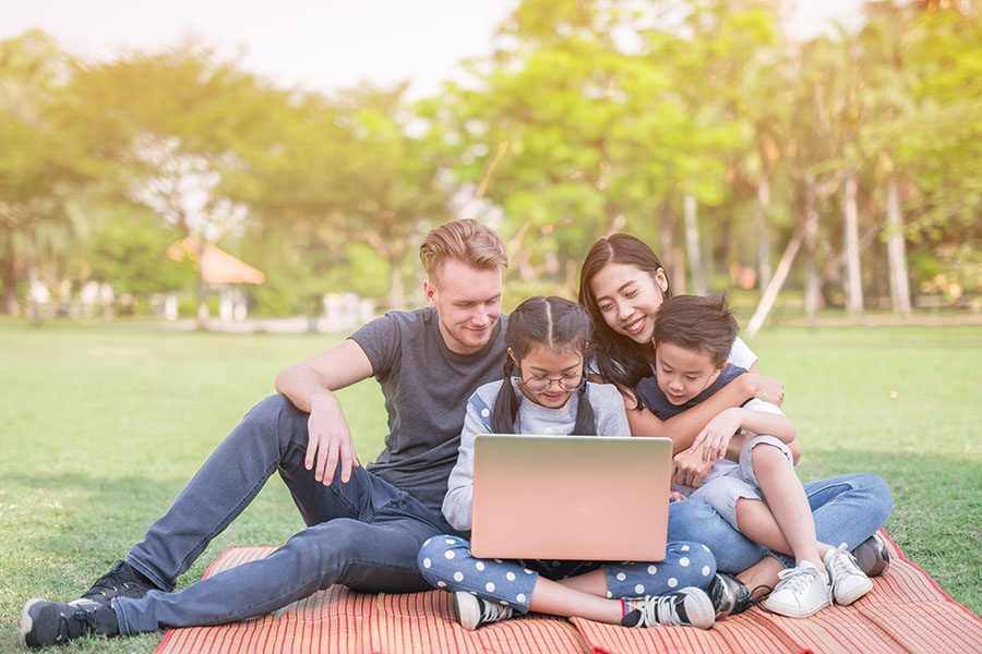 Blog - Family With Kids Sitting In The Park Using Their Laptop