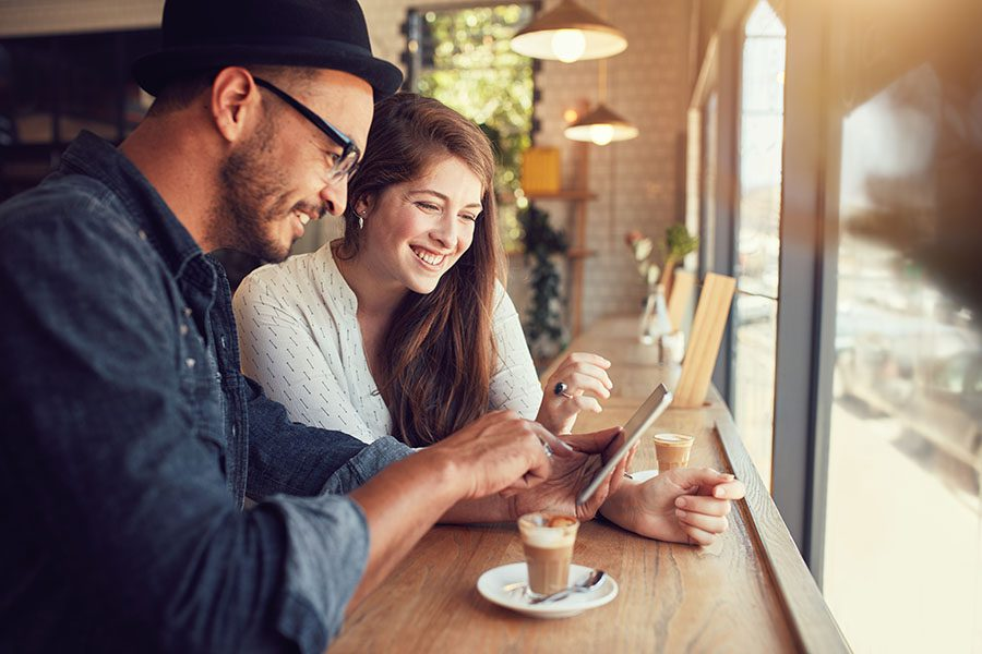 Client Center - Smiling Young Couple Using Tablet In A Modern Cafe