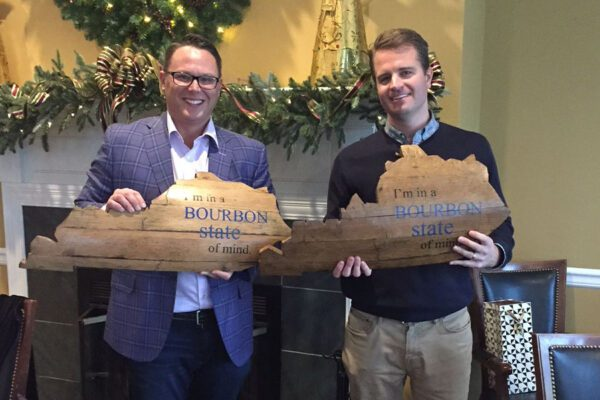 About Our Agency - Portrait of Byrne Insurance Group Agency Owners Holding Bourbon Kentucky Shaped State Signs
