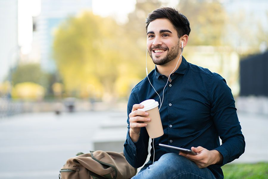Client Center - Smiling Young Man Using Digital Tablet Outdoors While Holding a Coffee Cup