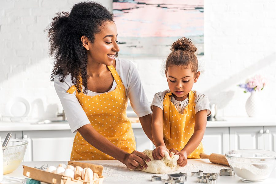 Employee Benefits - Portrait of Mother and Daughter Kneading Dough in Their Modern and Updated Kitchen on a Sunny Day