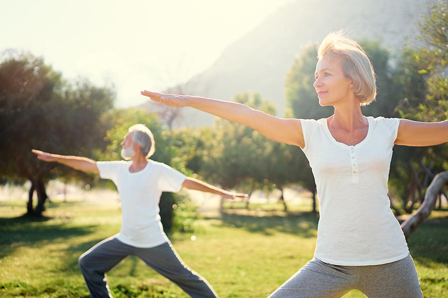 Health Insurance - Senior Couple Exercising and Doing Yoga at a Local Park Outdoors on a Summer Day at Dusk