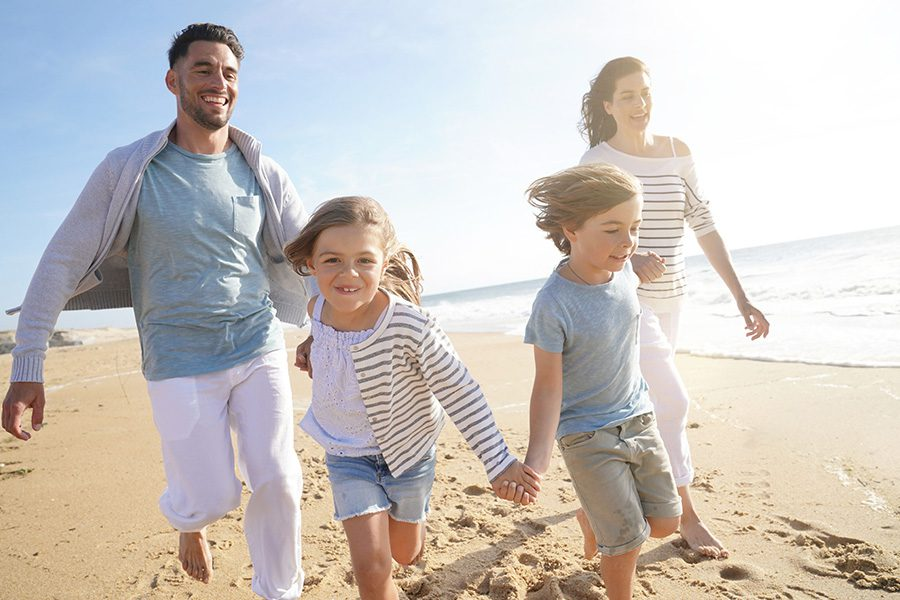 Personal Insurance - Happy Family Running on a Sandy Beach at Sunset