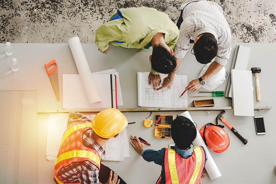 Specialized Business Insurance - View of a Group of Contractors and Engineers Planning New Building Blueprints and Design