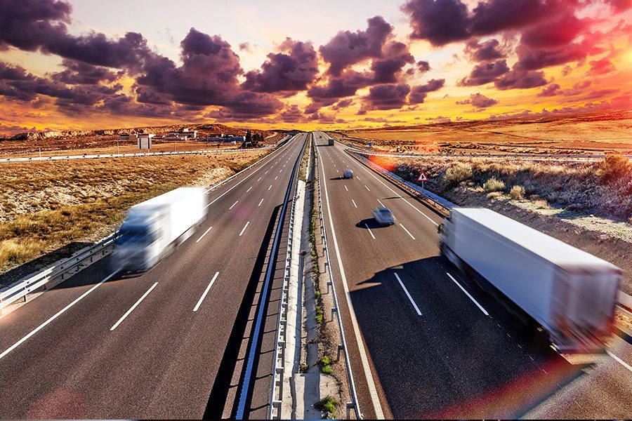 Transportation Insurance - Blurred View of a Long Stretch of Highway with Trucks and Cars Traveling in Both Directions at Dusk