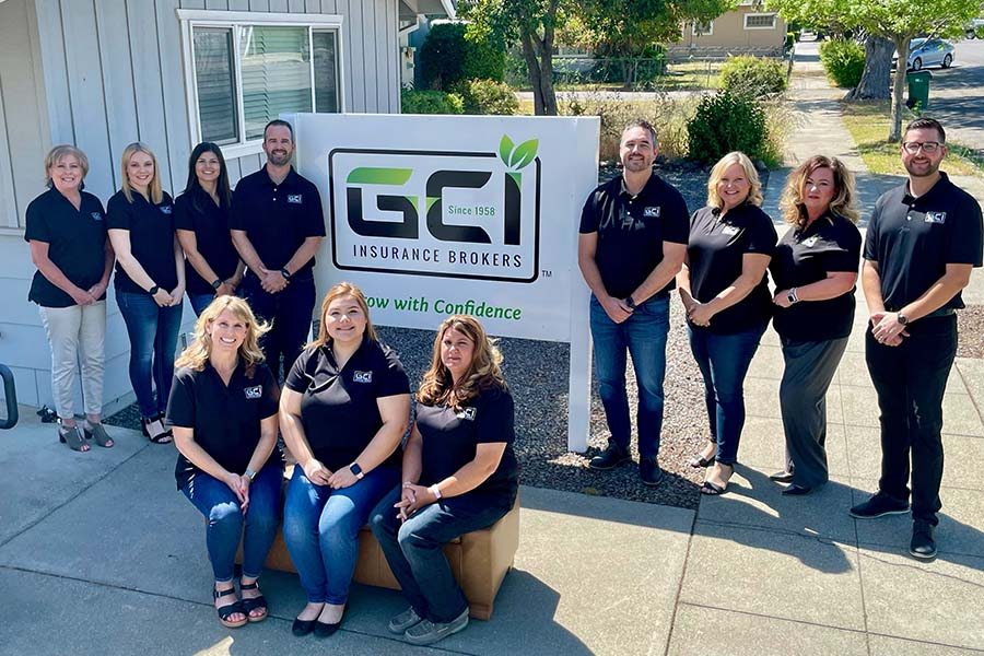 About Our Agency - Portrait of GCI Insurance Brokers Staff Outside the Office Building Next to a Sign with the GCI Logo