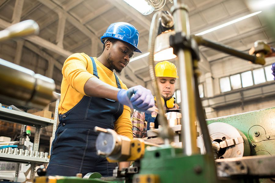 Business Insurance - Portrait of Two Factory Workers Using Heavy Mechanical Equipment While at Work