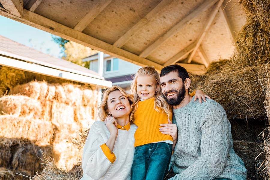 Personal Insurance - Portrait of a Cheerful Family with a Young Daughter Sitting on Hay in a Farm Building at Home