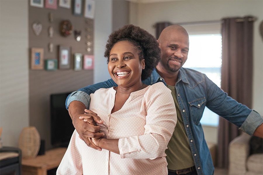 Individual Life and Health Insurance - Portrait of a Cheerful Middle Aged Woman Having Fun Dancing wiith Her Husband at Home in the Living Room