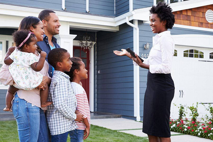 Blog - Close View of a Real Estate Agent Showing a Family a House on a Sunny Day