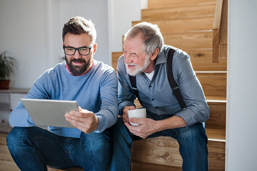 Client Center - An Adult Son and Senior Father With a Tablet Sitting on Stairs Inside Their Home