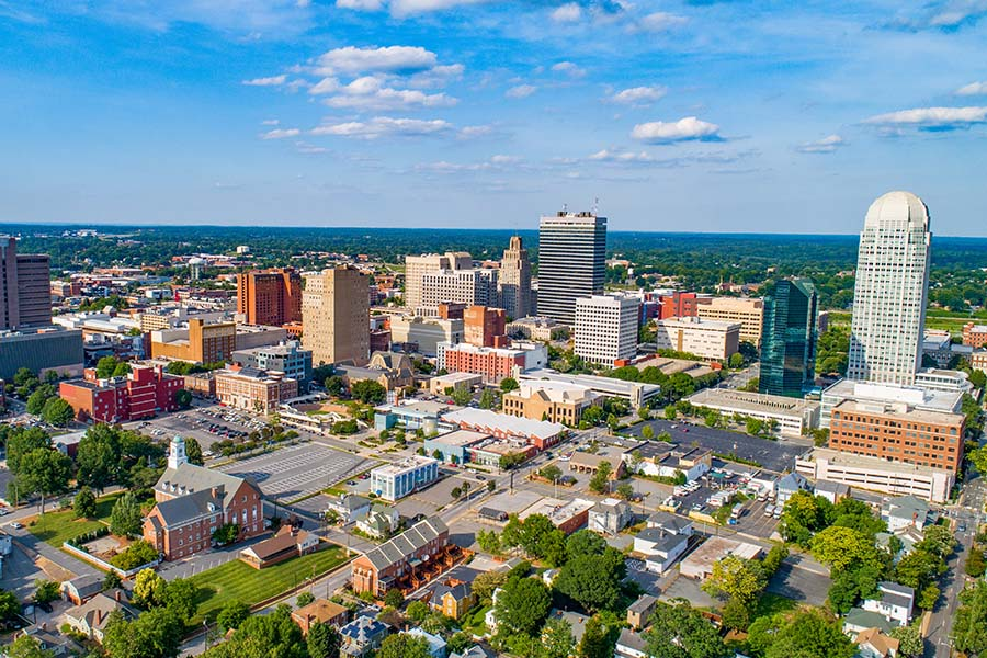 Contact - Aerial View of Downtown Winston-Salem, North Carolina Displaying Buildings and Trees on a Sunny Day
