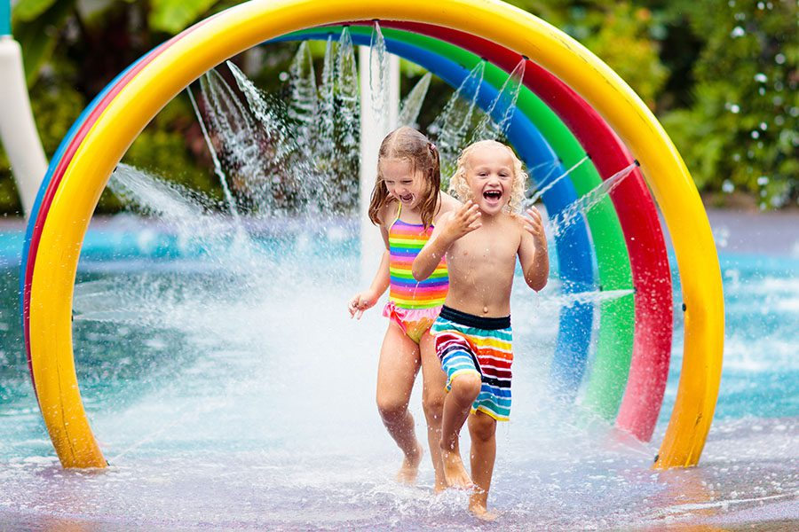 Personal Insurance - Happy Kids Running Through a Sprinkler at a Water Park