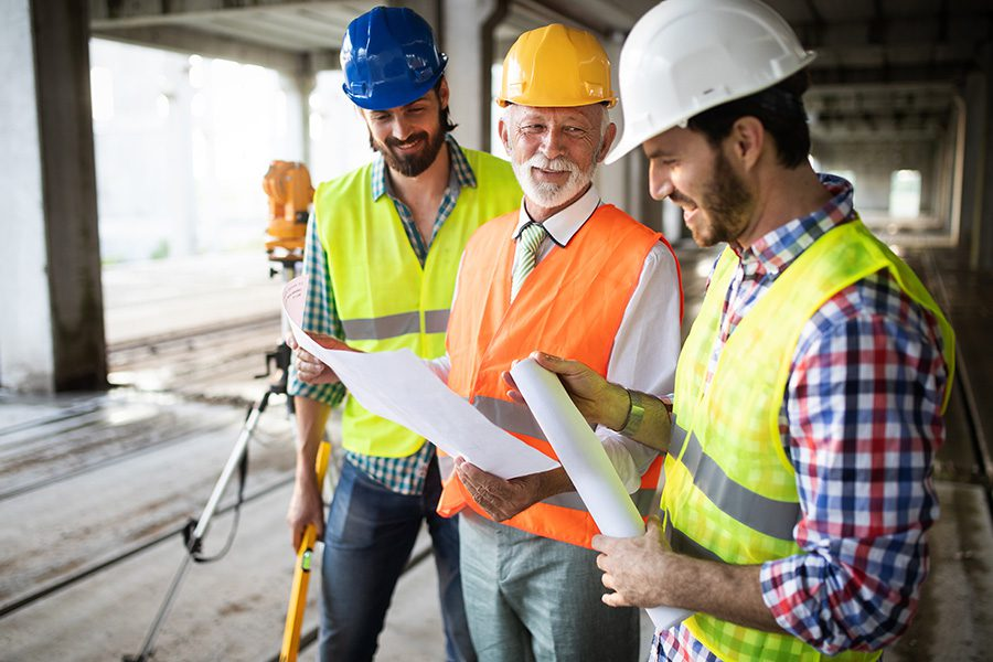 Specialized Business Insurance - Group of Construction Engineers Standing Together at a Construction Site Discussing Site Plans