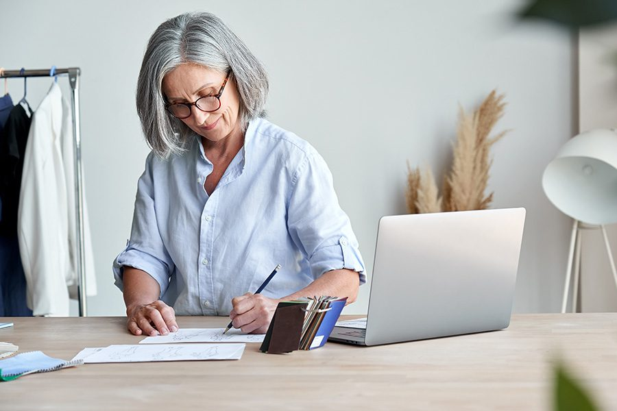 Business Insurance - Middle Aged Fashion Design Business Owner Working on Some Design Sketches in Her Studio