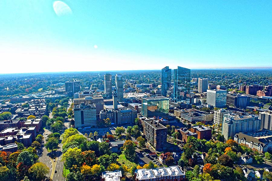 Contact - Aerial View of Downtown White Plains New York Surrounded by Colorful Trees on a Sunny Day