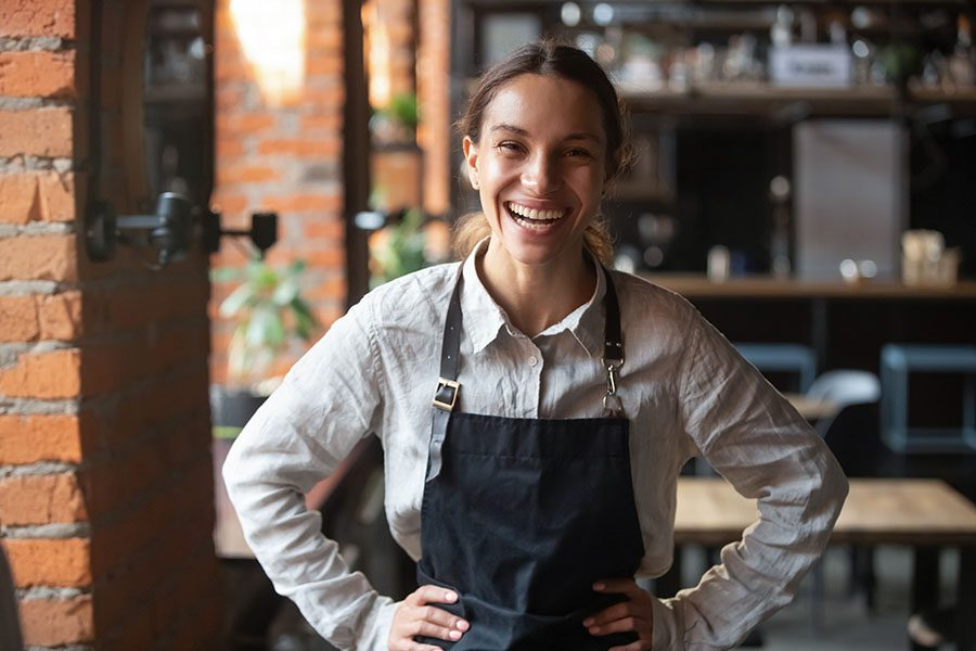 Specialized Business Insurance - Portrait of a Smiling Young Female Waitress Standing in a Restaurant with Her Arms on Her Hips