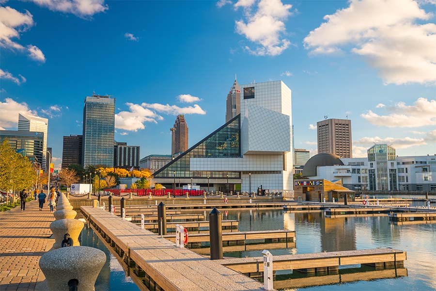 About Our Agency - Scenic View of Modern Buildings in Downtown Cleveland Ohio Next to the River with Boat Docks Against a Bright Blue Sky