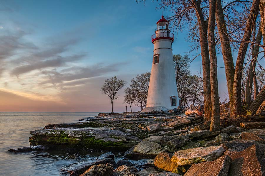 Client Center - Scenic View of a Lighthouse Next to the Coast Along Lake Erie at Sun Down with a Colorful Sky