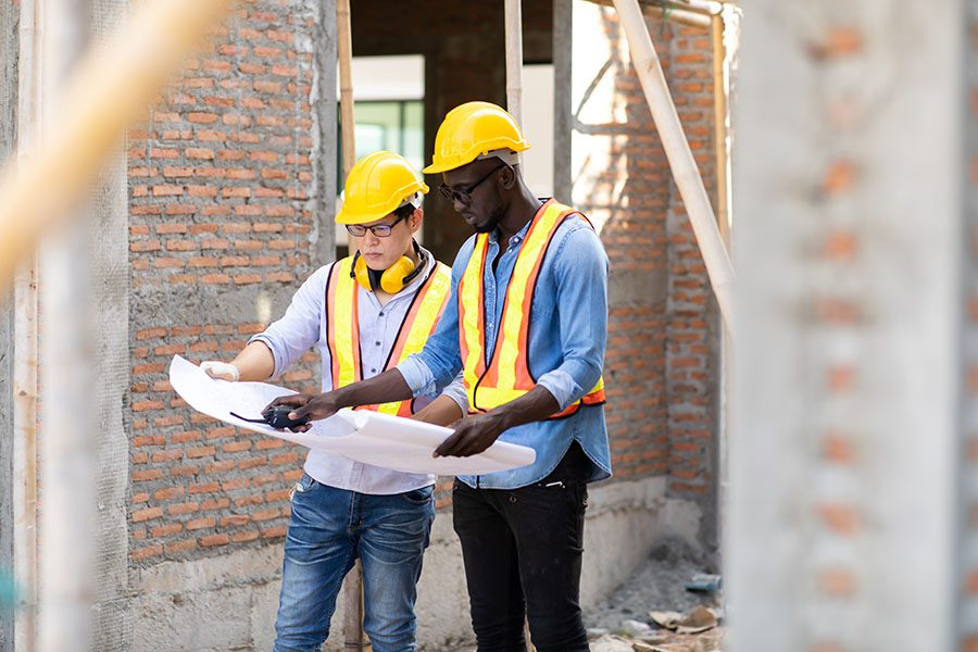 Specialized Business Insurance - Portrait of Two Contractors Standing on a Commercial Jobsite While Inspecting the Building Blueprints
