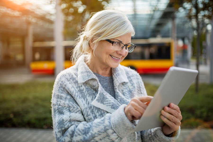 Video Library - Closeup Portrait of a Smiling Elderly Woman Standing Outside a Building in the City While Using a Tablet
