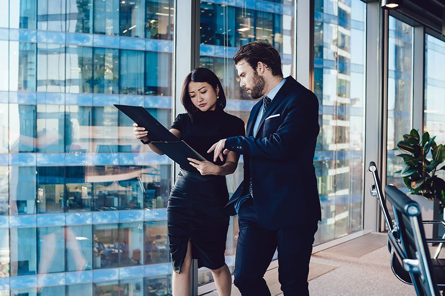 Business Insurance - Business Man and Woman Walking Through an Office While Discussing About Documents the Woman is Holding
