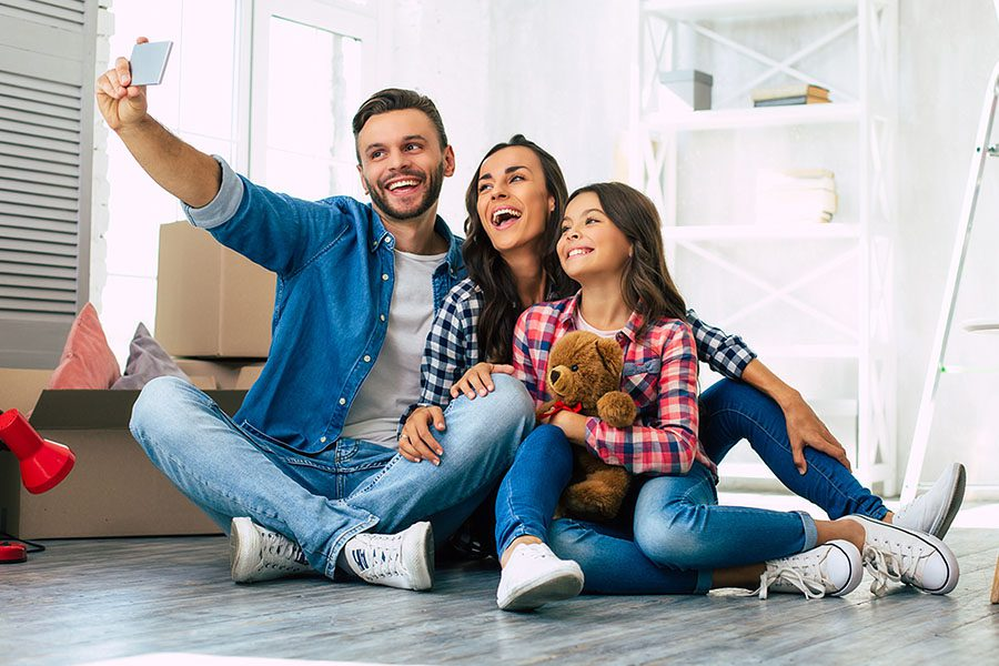 Personal Insurance - A Young Family of a Father, Mother and Daughter Sitting on the Floor of Their New Home Taking a Selfie and Laughing Together