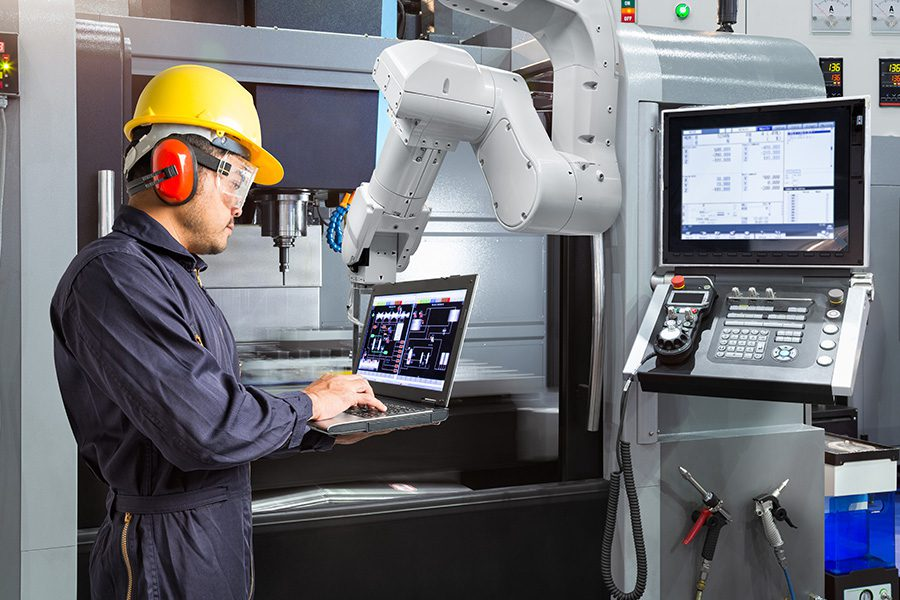 Specialized Business Insurance - A Maintenance Engineer is Using a Laptop to Control an Automatic Robotic Hand in a Smart Factory
