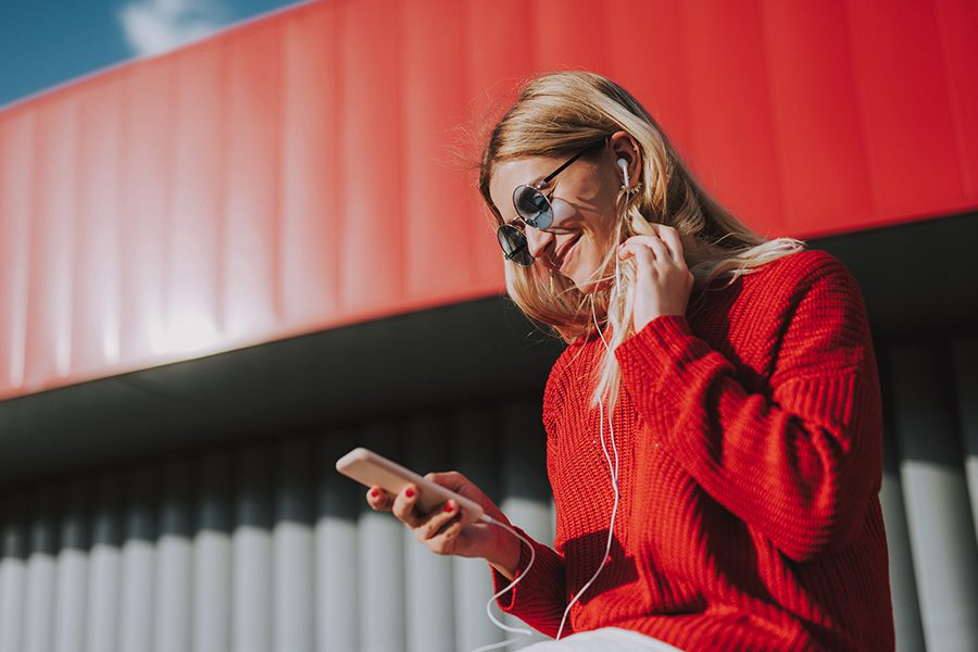 Video Library - Side View Portrait of a Woman Wearing a Red Sweater With Earphones on Watching Videos on Her Smartphone and Smiling
