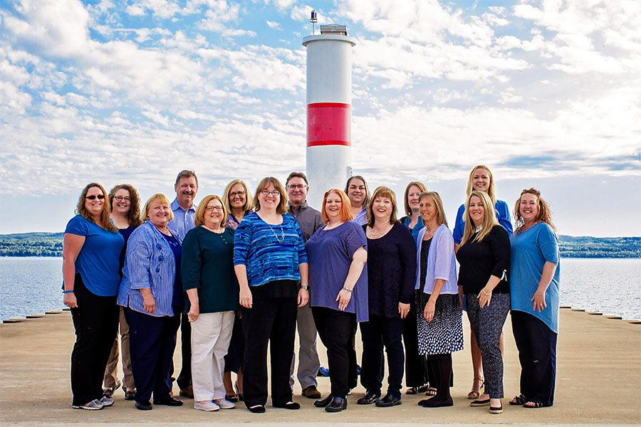 About Our Agency - Portrait of the Harbor Brenn Insurance Agencies Staff Standing in Front of the Lighthouse on the Harbor in Petoskey Michigan