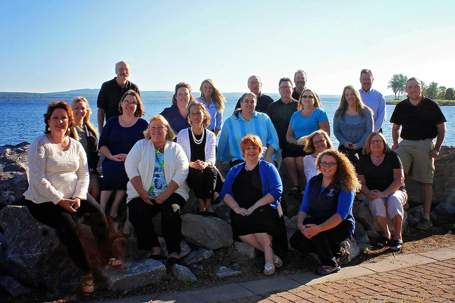About Our Agency - Portrait of the Harbor Brenn Insurance Agencies Team Sitting on Rocks By the Coast on a Sunny Day in Petoskey Michigan