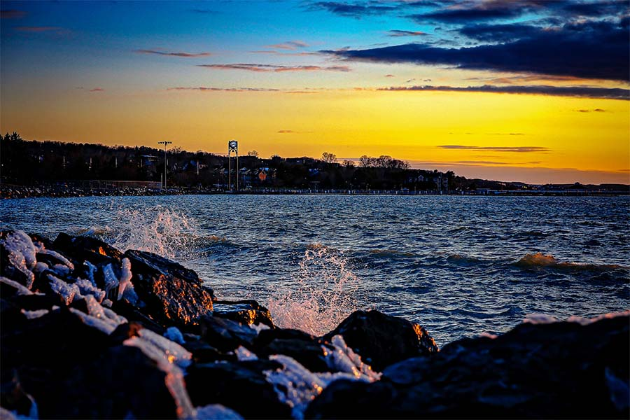 About Our Agency - Scenic View of the Waves Splashing Against the Rocks on the Coastline of Petoskey Michigan at Sundown