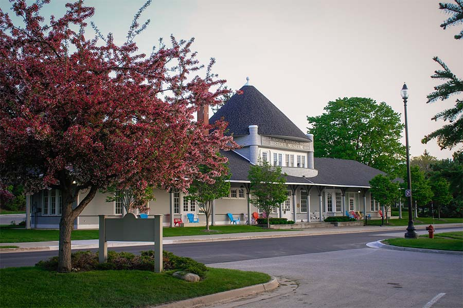 About Our Agency - View of History Museum Building Next to Blooming Tree in Petoskey Michigan