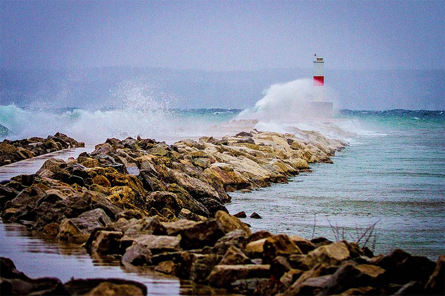 About Our Agency - View of Waves Crashing into Lighthouse and Jetty in Petoskey Michigan