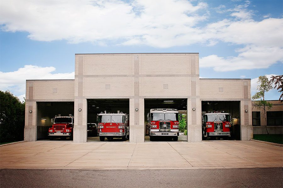 About Our Agency - View of the Fire Station with Parked Fire and Emergency Trucks Against a Cloudy Sky in Petoskey