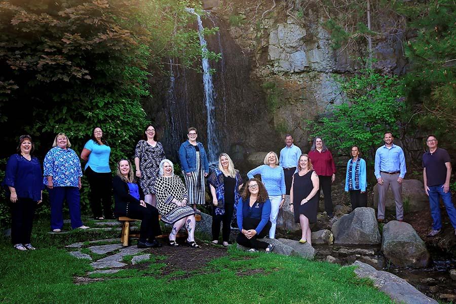 Our Culture - Portrait of the Harbor Brenn Insurance Agencies Team in Front of a Scenic Waterfall