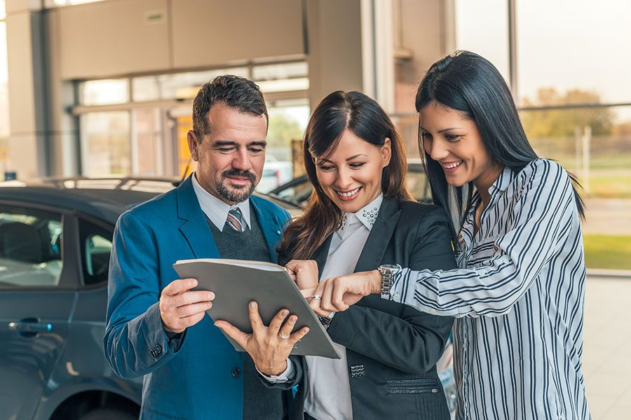 Auto Change Information Form - Portrait of a Smiling Car Dealership Sales Agent Showing Her Two Clients the Contract for Their New Car Purchase