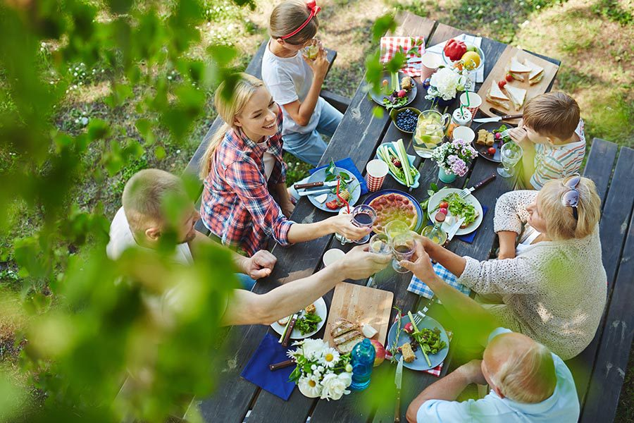 About Our Agency - Family Having Dinner Outdoors at a Picnic Table, Seen From Above Between Tree Branches