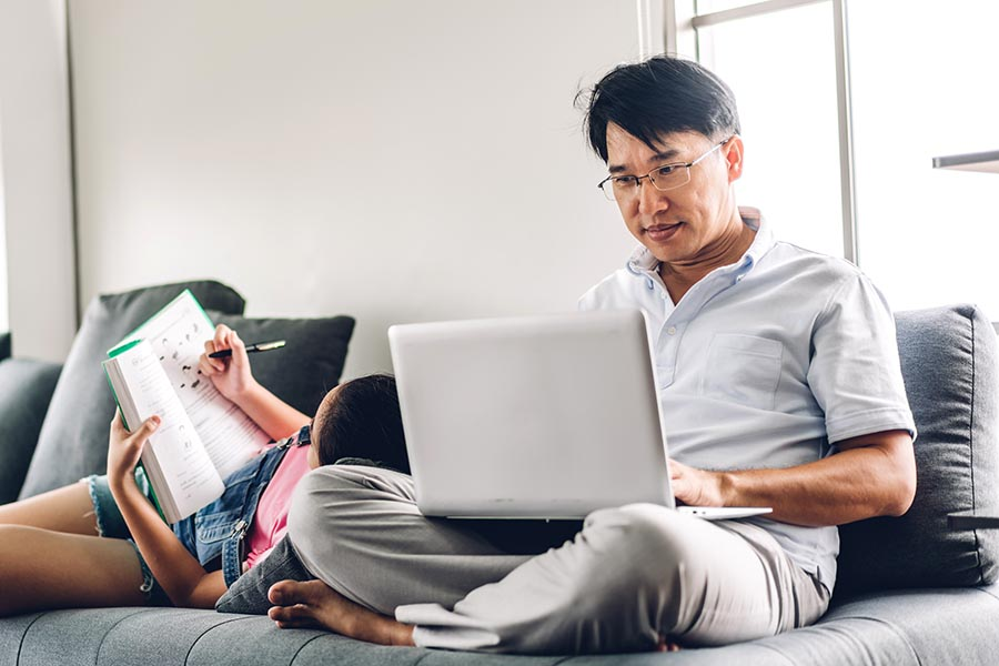 Client Center - Dad Using a Computer on the Couch While His Daughter Does Homework Next to Him