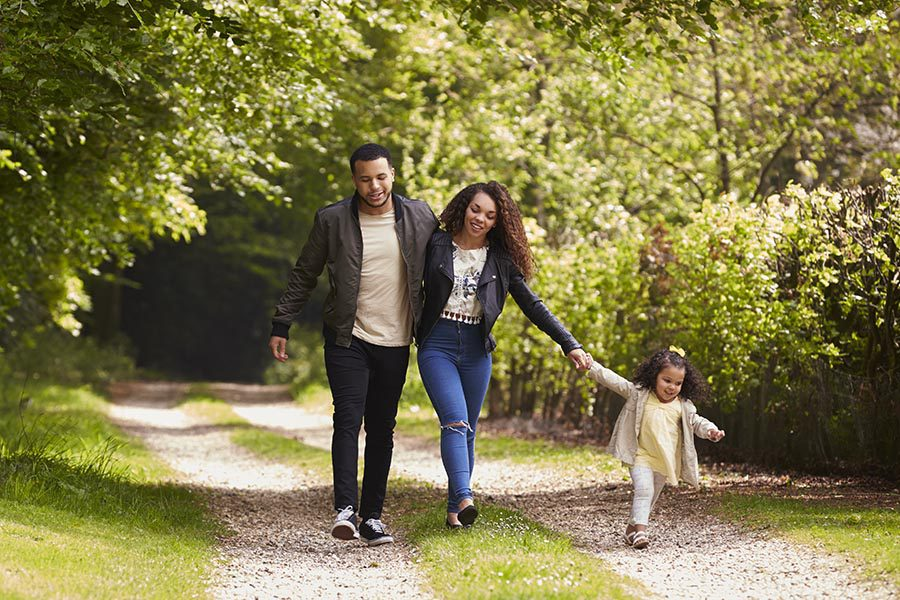 Personal Insurance - Mother, Father and Young Daughter Walking Down a Path in a Green Park